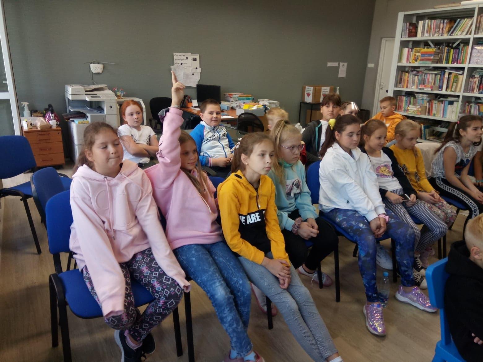 Uczniowie klasy 4b siedzący w bibliotece