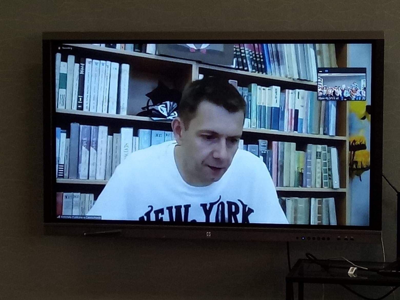 Tablica multimedialna z widocznym Rafałem Witkiem- pisarzem na tle książek
