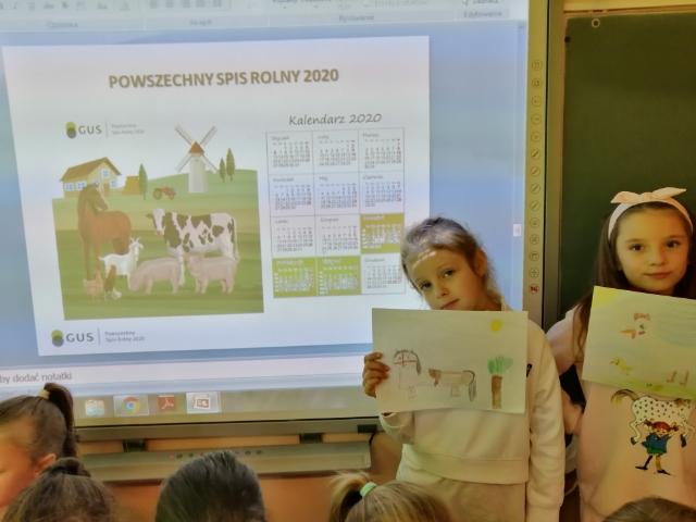 uczennice klasy 1a natle tablicy interaktywnej wyświetlającej slajd zprogramu Powszechny spis rolny
