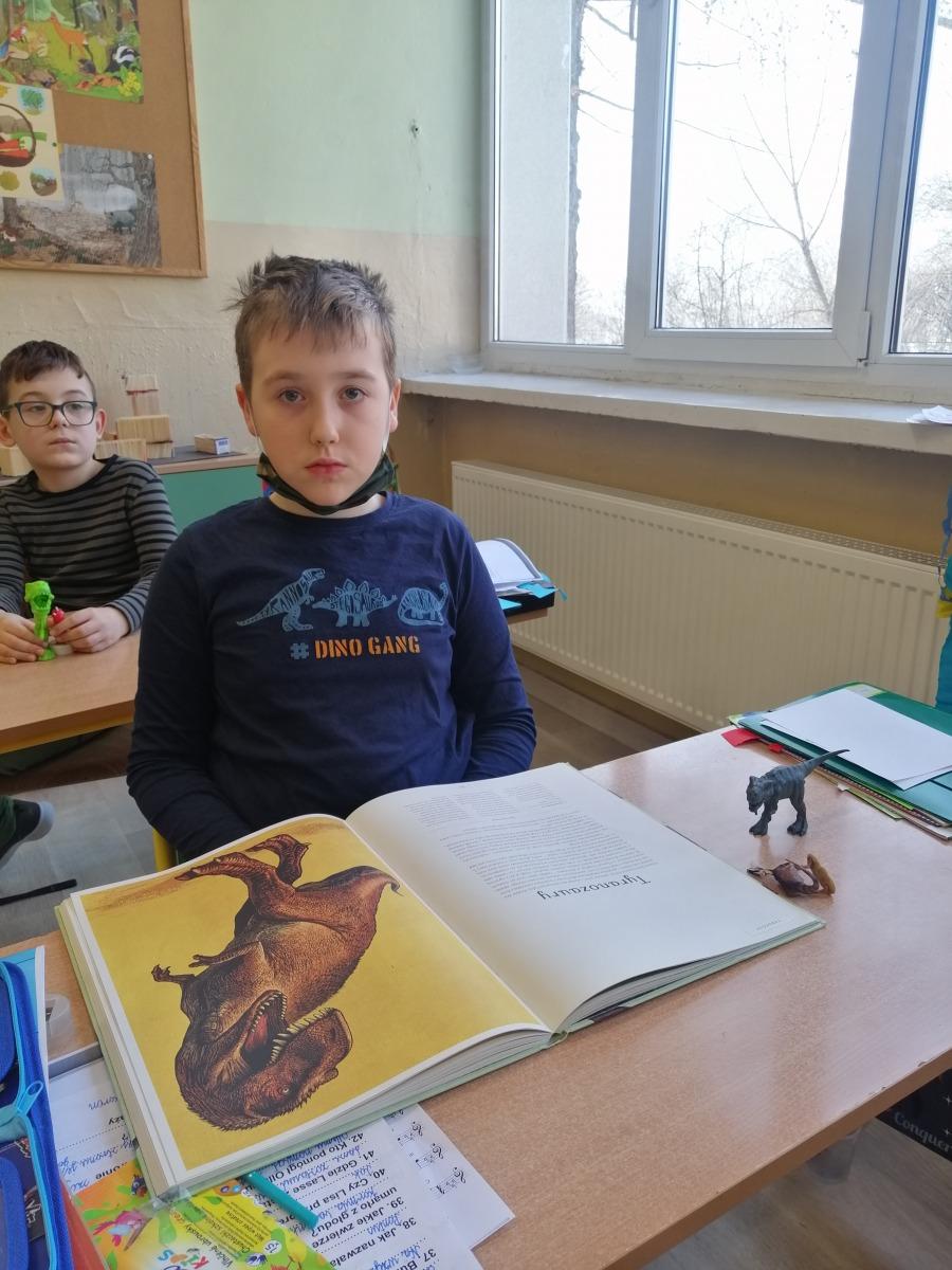 Chłopiec prezentujący ksiązki o dinozaurach