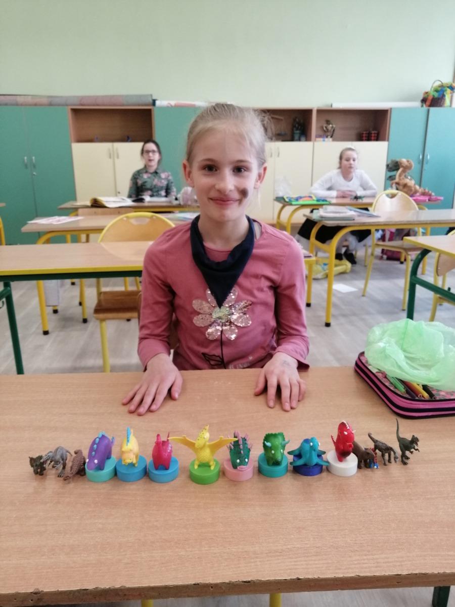 Dziewczynka prezentująca figury dinozaurów