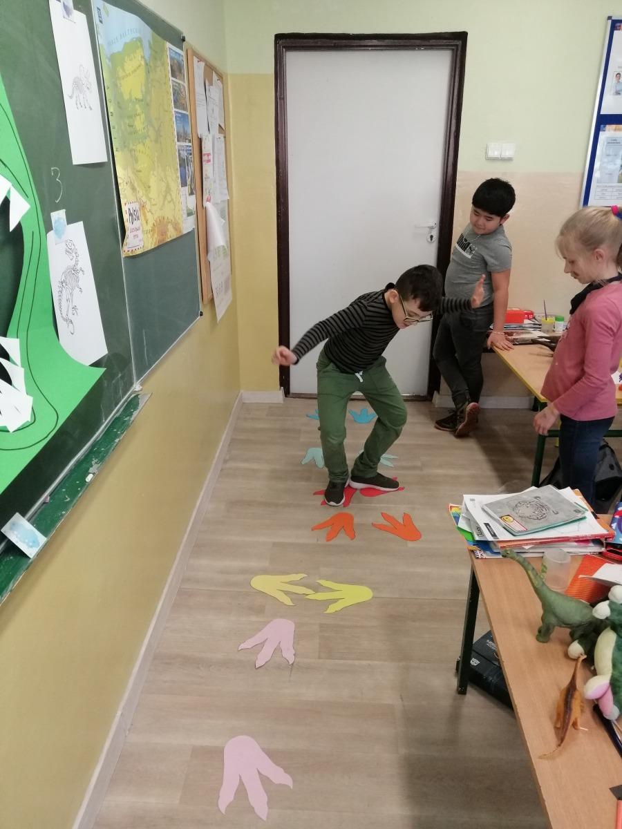 uczniowie skaczący po śladach dinozaurów